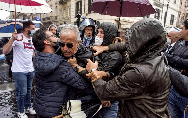 A demonstrator is arrested in Rome during protests against the economic situation in Italy during the lockdown exit strategy - Stefano Montesi - Corbis/Corbis News