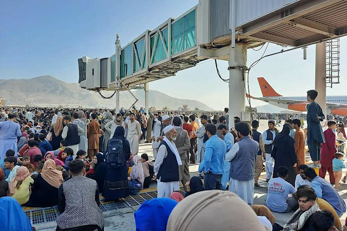 Afghans crowd at the tarmac of the Kabul airport on August 16, 2021, to flee the country as the Taliban were in control of Afghanistan after President Ashraf Ghani fled the country and conceded the insurgents had won the 20-year war. (AFP via Getty Images)