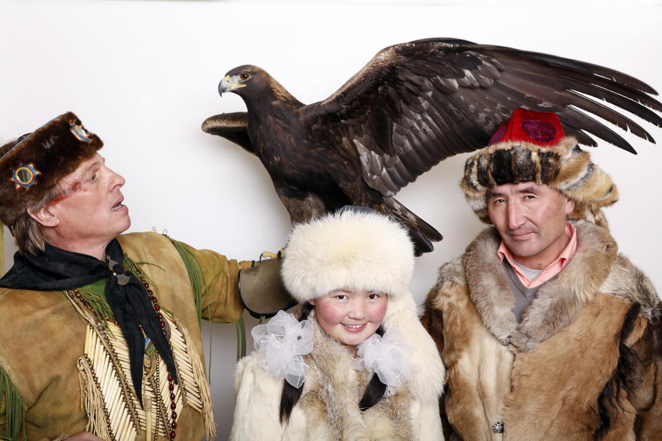 """Eagle Huntress, Ashol-Pan, center, poses with her father and an eagle for a portrait to promote the film, """"Eagle Huntress"""", at the Toyota Mirai Music Lodge during the Sundance Film Festival on Saturday, Jan. 23, 2016 in Park City, Utah. (Photo by Matt Sayles/Invision/AP)"""