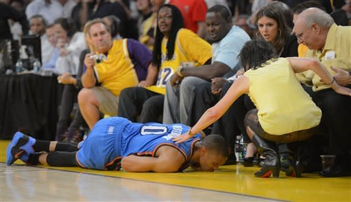 Oklahoma City Thunder guard Russell Westbrook lays on the floor as a fan checks on him during the first half in Game 4 of an NBA basketball playoffs Western Conference semifinal against the Los Angeles Lakers, Saturday, May 19, 2012, in Los Angeles. (AP Photo/Mark J. Terrill)