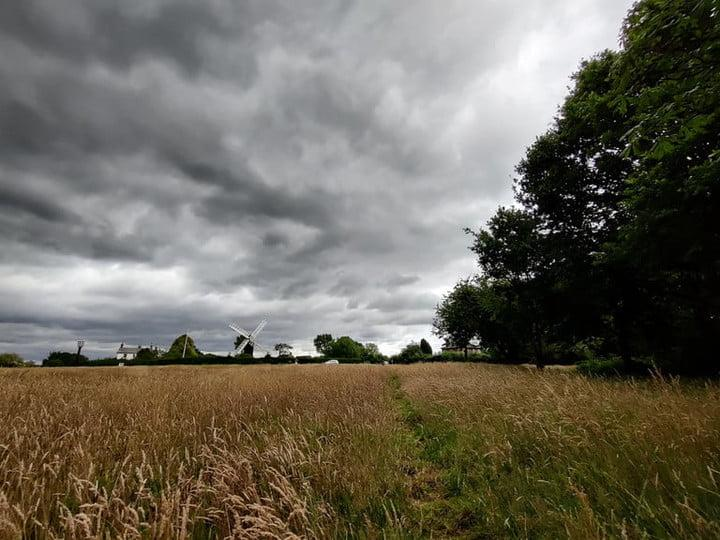 image taken with OnePlus Nord showing a field with a very cloudy sky and very gray clouds