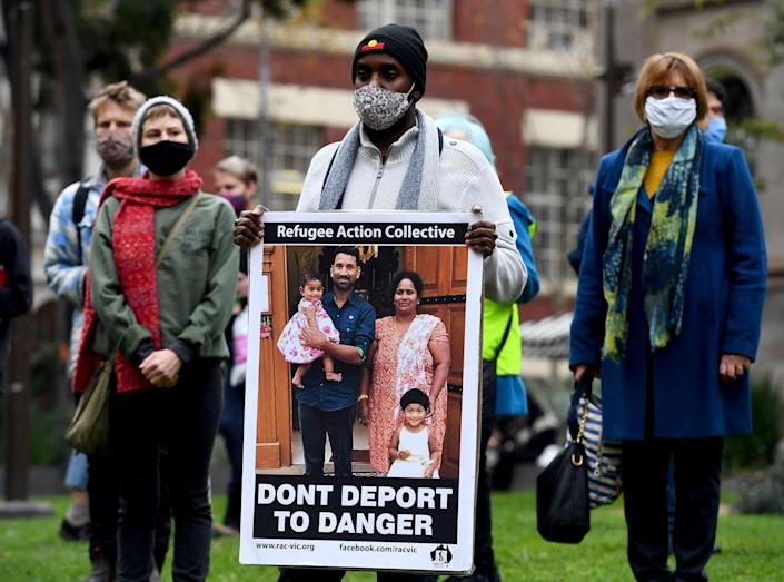 People hold up placards at a rally to support the Sir Lankan origin Tamil family living in detention  (AFP via Getty Images)