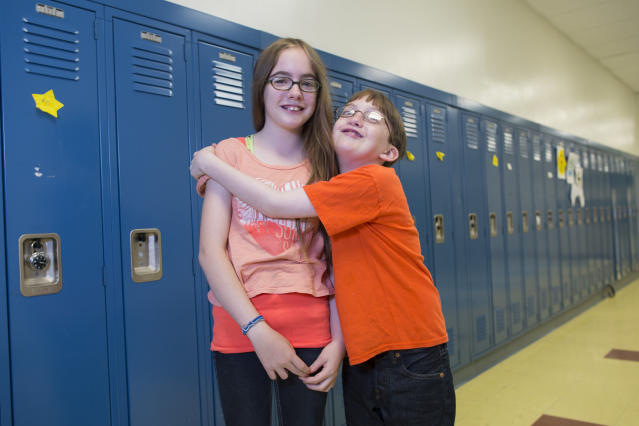 In this Thursday, June 6, 2013 photo, Jamie Flaherty, left, and her twin brother, O'Ryan, one of the twenty-four sets of twins from Highcrest Middle School in Wilmette, Ill. pose for a portrait at the school,. The group is attempting to break a Guinness World record for the amount of twins in one grade which is currently 16 sets. (AP Photo/Scott Eisen)