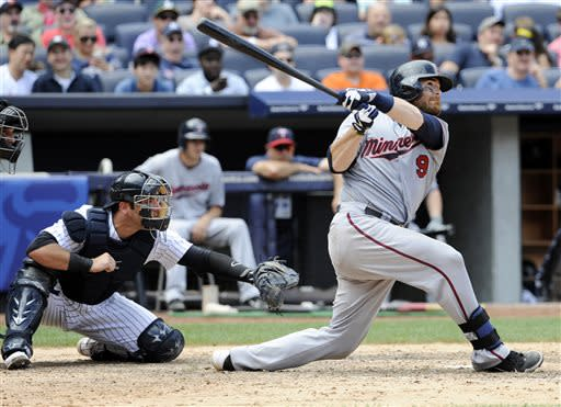 Minnesota Twins' Ryan Doumit follows through on a home run as New York Yankees catcher Austin Romine, left, looks on during the seventh inning of a baseball game Saturday, July 13, 2013, at Yankee Stadium in New York. (AP Photo/Bill Kostroun)