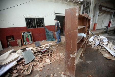A resident stands near an image of the Virgin of Guadalupe and debris after an earthquake struck the southern coast of Mexico late on Thursday, in Juchitan, Mexico, September 10, 2017. REUTERS/Edgard Garrido