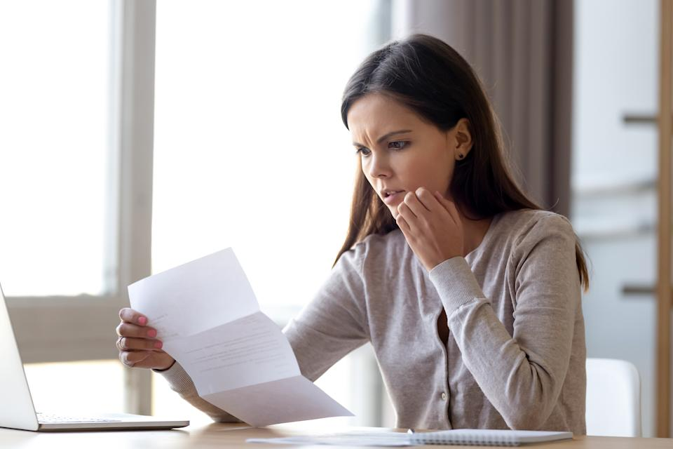 Disappointed young woman sit on table at home read bad news eviction notice in paperwork letter, shocked female surprised by unpleasant message warning notification received in paper mail