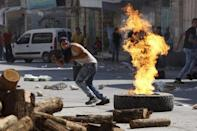 A Palestinian protester runs during clashes with Israeli troops following a protest against the Israeli police raid on Jerusalem's al-Aqsa mosque on Tuesday, in the occupied West Bank city of Hebron September 18, 2015. REUTERS/Mussa Qawasma