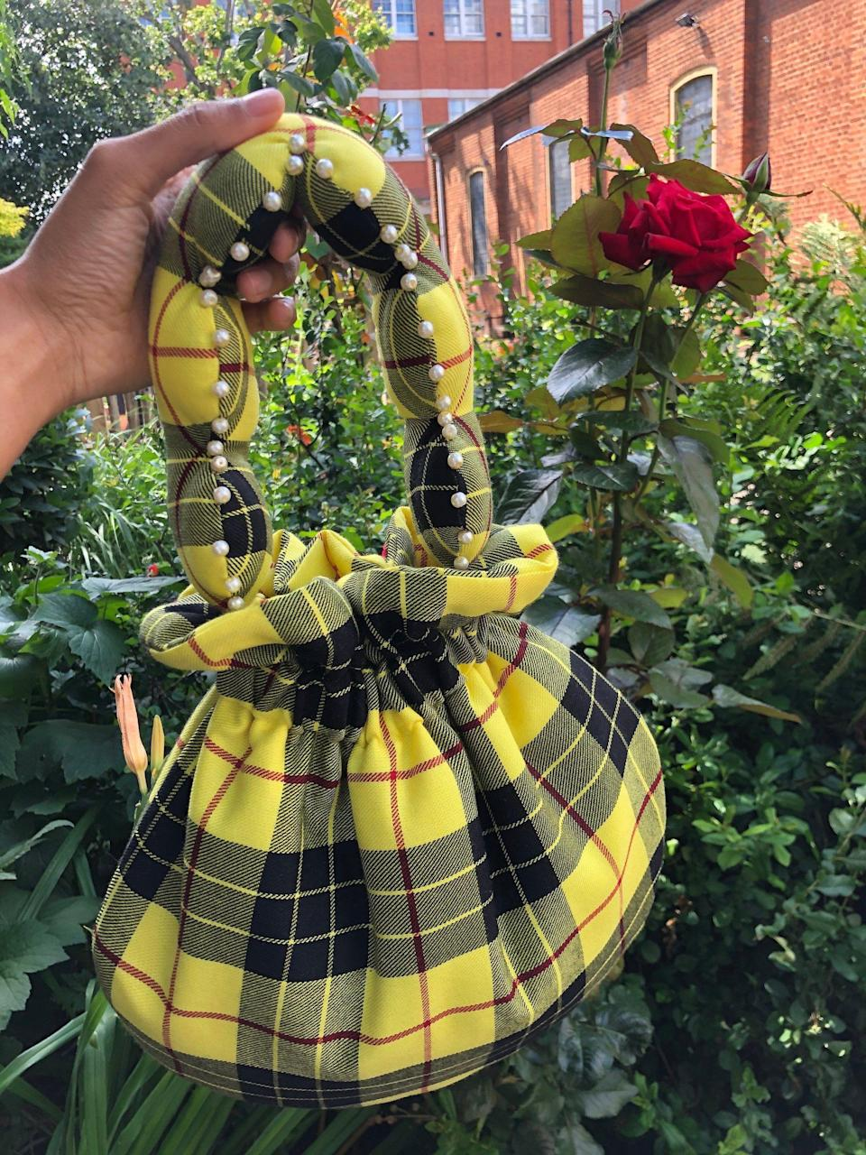 """<p><strong>Flat Fifteen</strong></p><p>flatfifteen.co.uk</p><p><strong>£75.00</strong></p><p><a href=""""https://flatfifteen.co.uk/products/yellow-black-tartan-scallop-handle-bag"""" rel=""""nofollow noopener"""" target=""""_blank"""" data-ylk=""""slk:SHOP IT"""" class=""""link rapid-noclick-resp"""">SHOP IT</a></p><p>This super sweet lil' puffy bag, inspired by those """"your Aunty would probably wear to Church on a Sunday,"""" is made from remnant and vintage fabric and beads from used jewelry. It's puffed up from stuffing used to fill toys and furniture.</p>"""