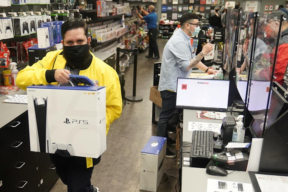 Inside a GameStop store a worker takes a Sony PS5 gaming console to the counter to sell in the Manhattan borough of New York City, New York, U.S., November 12, 2020. REUTERS/Carlo Allegri