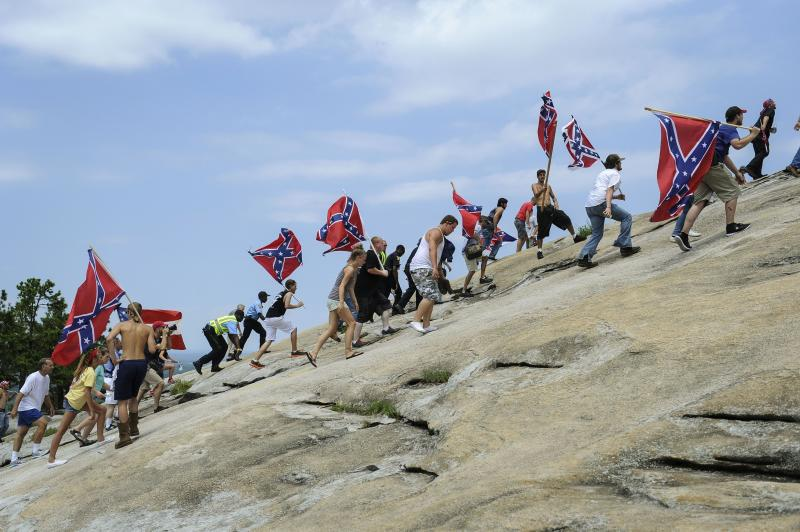 """FILE - In this Aug. 1, 2015 file photo, Confederate flag supporters climb Stone Mountain to protest of what they believe is an attack on their Southern heritage during a rally at Stone Mountain Park in Stone Mountain, Ga. The sculpture of Gen. Robert E. Lee, Confederate President Jefferson Davis and Gen. Thomas J. """"Stonewall"""" Jackson on the face of Stone Mountain is America's largest Confederate memorial. (AP Photo/John Amis, File)"""
