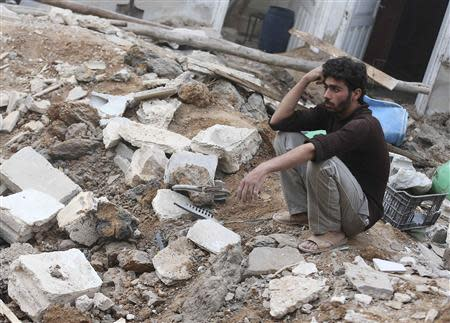 A man sits on the rubble of the damaged buildings by what activists said was an air strike by forces loyal to Syrian President Bashar al-Assad in the Duma neighbourhood of Damascus