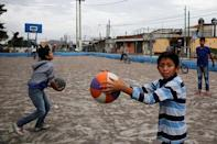 Children play at a basketball court covered with ash after Guatemala's Fuego volcano erupted violently, in Guatemala City, Guatemala June 3, 2018. REUTERS/ Luis Echeverria