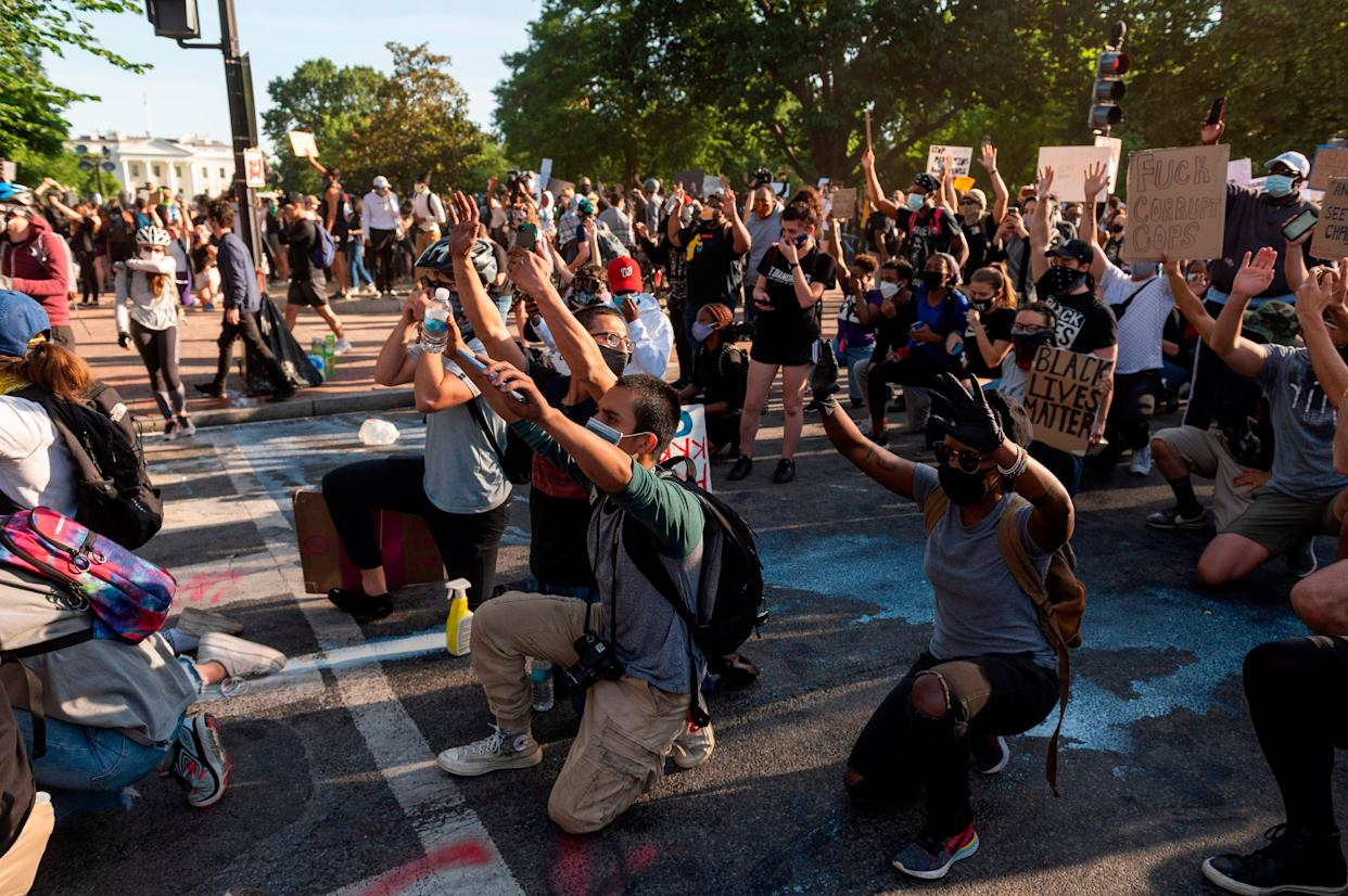 Protestors take a knee and raise their hands as they face riot police near the White House on June 1 as demonstrations against George Floyd's death continue.
