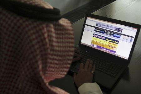 A Saudi man explores a website on his laptop in Riyadh