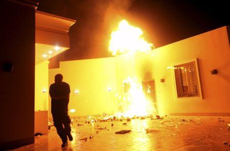 The U.S. Consulate in Benghazi is seen in flames during a protest by an armed group said to have been protesting a film being produced in the United States, in this September 11, 2012 file photo. Partly burned and still abandoned, the high-walled villas that once housed the U.S. consulate compound in the Libyan city of Benghazi now sit on a frontline of a nation at war with itself. Three years after militants killed U.S. ambassador Christopher Stevens and three other Americans in an attack on the facility, Benghazi is back in U.S. news headlines as White House contender and former secretary of state Hillary Clinton faces a Congressional hearing on the incident on October 22, 2015. For Libyans and Benghazi, though, the war never really disappeared. After their democratic hopes were kindled following the 2011 revolt against Muammar Gaddafi, Libya has steadily spiralled into chaos among a myriad of armed factions. To match story LIBYA-SECURITY/BENGHAZI       REUTERS/Esam Al-Fetori/Files
