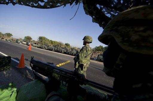Two Mexican soldiers stand guard at a checkpoint on the road that links Navolato and Los Mochis, in Sinaloa State