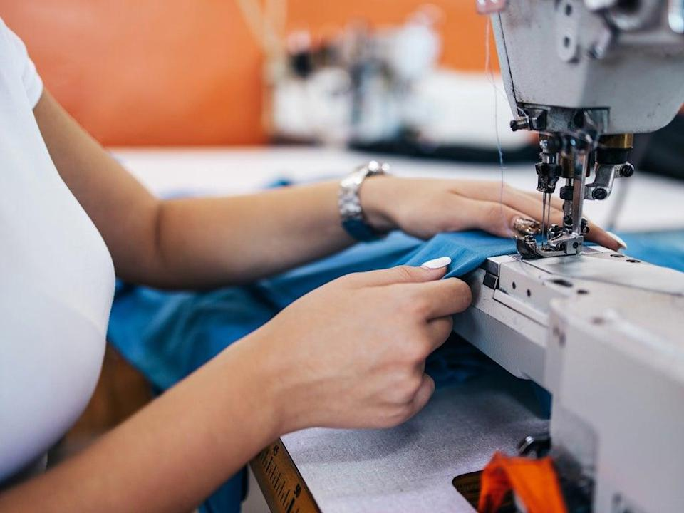 A person repairs a piece of clothing with a sewing machine (Getty Images)