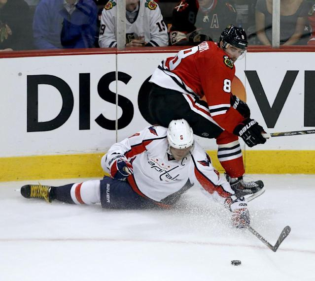 Washington Capitals right wing Alex Ovechkin, left, and Chicago Blackhawks defenseman Nick Leddy compete for a loose puck during the third period of an NHL hockey game Tuesday, Oct. 1, 2013, in Chicago. The Blackhawks won 6-4. (AP Photo/Charles Rex Arbogast)