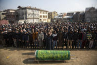 Kashmiri Muslims offer funeral prayers near the coffin of Basharat Ahmad Zargar in Srinagar, Indian-controlled Kashmir, Sunday, Feb.14, 2021. Zargar, who was working at a power project, was among the dozens killed after a part of a Himalayan glacier broke off on February 7 sending a devastating flood downriver slamming into two hydropower projects in northern India. (AP Photo/Mukhtar Khan)