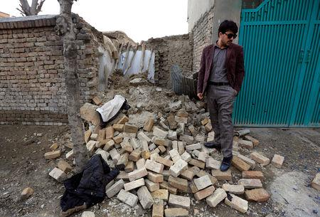 A man stands near the debris at one of the explosion sites in Kabul