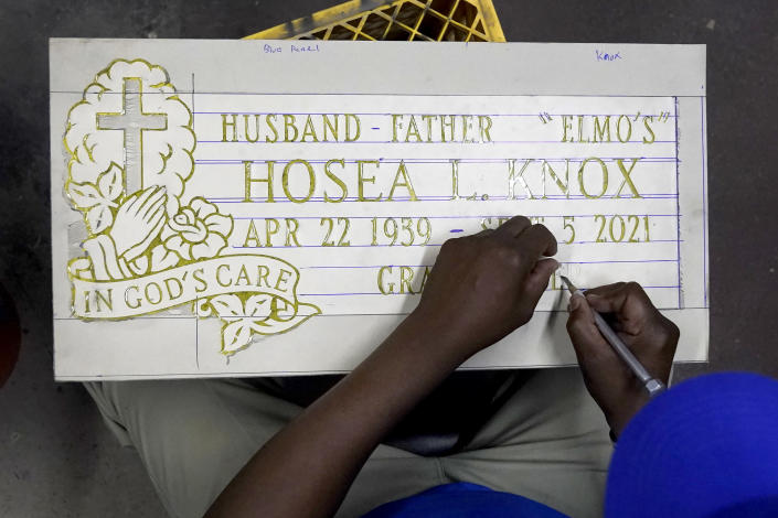 Leon Brown, long time assistant to Hosea Knox, owner of Elmo's Tombstone Service, works on the tombstone of the recently deceased Knox, on the South Side of Chicago, Tuesday, Sept. 14, 2021, one day after Knox's funeral. (AP Photo/Charles Rex Arbogast)