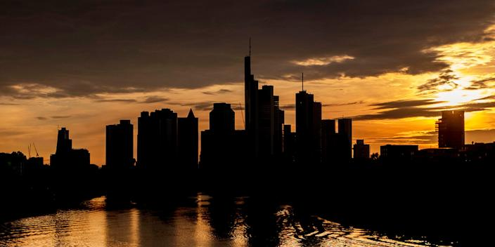 The sun sets behind the buildings of the banking district in Frankfurt, Germany, Saturday, May 9, 2020. (AP Photo/Michael Probst)