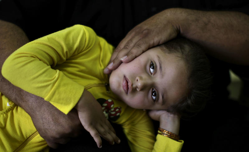 Syrian Mohammed Ramadan, 46, whose displaced from his home in Dir el Zour, due to fighting between the rebels and government forces, comforts his daughter Haneen, 5, who suffers from a lung infection, while waiting to be examined by a doctor at a makeshift hospital in Suran, on the outskirts of Aleppo, Syria, Monday, Sept. 10, 2012. (AP Photo/Muhammed Muheisen)