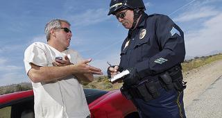 Police officer writing ticket for man with red convertible  copyright bikeriderlondon/Shutterstock.com