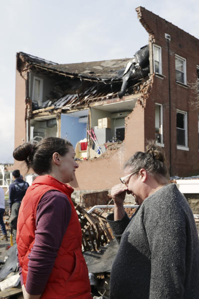 Debbie Jones, right, wipes tears as she views the damage to East End United Methodist Church after it was heavily damaged by a storm Tuesday, March 3, 2020, in Nashville, Tenn. Jones attended the church when she was a child.  Tornadoes ripped across Tennessee early Tuesday, shredding buildings and killing multiple people. (AP Photo/Mark Humphrey)