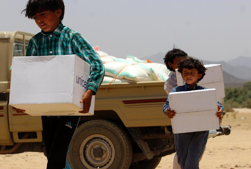 Displaced Yemeni children -- who fled the fighting between Huthi rebels and pro-regime militia -- carry boxes of humanitarian aid donated by UNICEF outside their shelter of Sirwah, on May 11, 2015