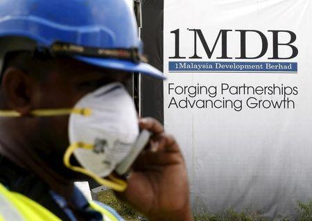 FILE PHOTO: A construction worker talks on the phone in front of a 1Malaysia Development Berhad (1MDB) billboard at the Tun Razak Exchange development in Kuala Lumpur, Malaysia