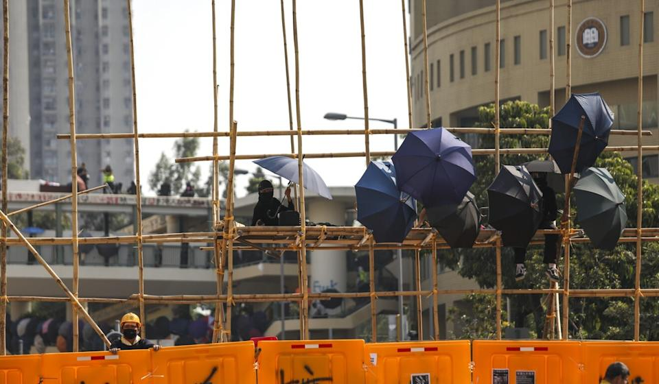 Protesters hold umbrellas on a scaffolding at Baptist University last year. Photo: Xiaomei Chen