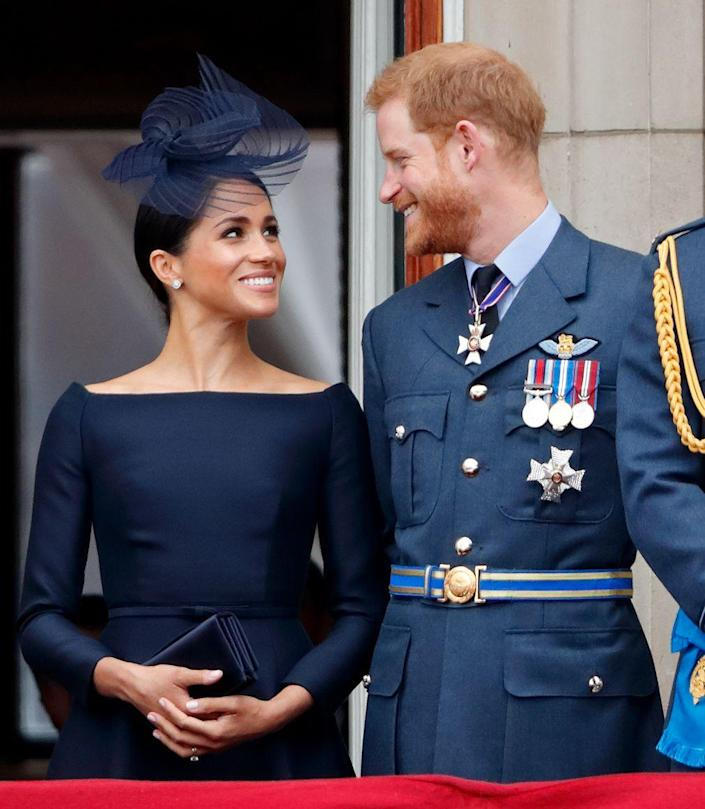 <p>Prince Harry and Meghan Markle looked true blue on the Buckingham Palace balcony, with Meghan's navy monochrome look pairing nicely with Harry's uniform.</p>