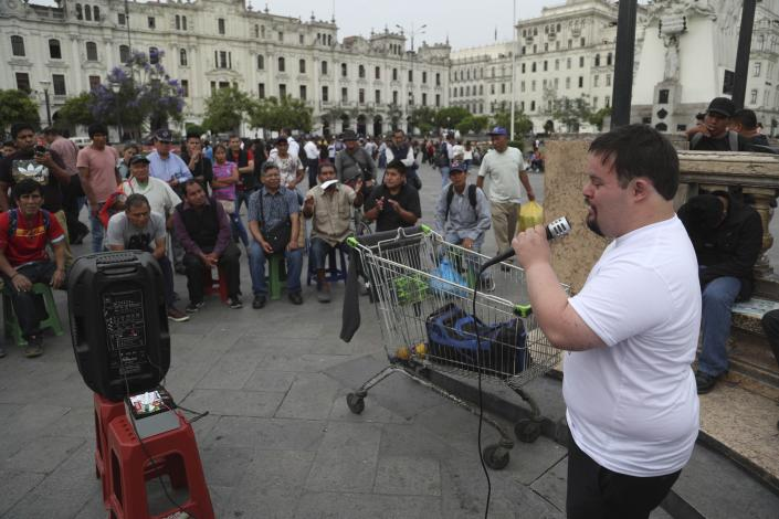 In this Dec. 13, 2019 photo, congressional candidate Bryan Russell campaigns at San Martin Plaza in Lima, Peru. Russell, who has Down syndrome, is a candidate for Peru-Nacion, a center-right party that is not widely known in Peru, but his bold campaign ahead of the Jan. 26 parliamentary elections is getting attention. (AP Photo/Martin Mejia)