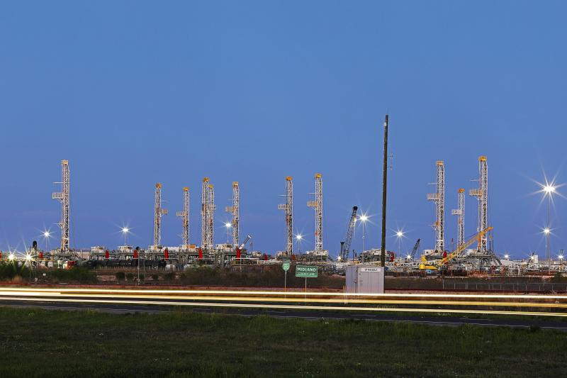 In this Thursday evening, April 2, 2020 photo, traffic passes over the Midland-Odessa county line in front of an oil rig storage yard. (Odessa American/Eli Hartman)