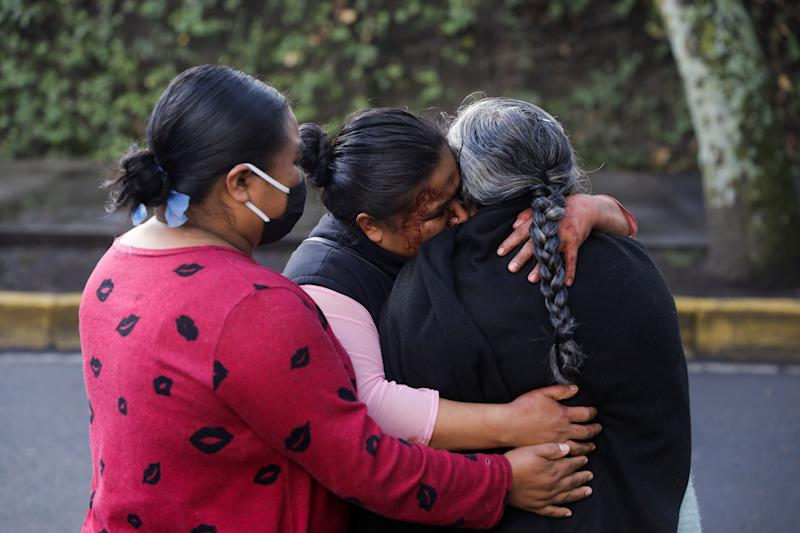 The relatives of a woman killed during a shooting react near a crime scene following an assassination attempt of Mexico City's chief of police Omar Garcia Harfuch, at the upscale neighborhood of Lomas de Chapultepec, in Mexico City, Mexico June 26, 2020. REUTERS/Luis Cortes