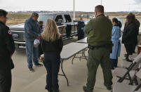 In this Thursday, April 29, 2021, photo, Sherry Cross Child and Shane Little Bear, residents of Stand Off, Alberta, recite a prayer ahead of a vaccination clinic held in Montana for Canadian residents at the Piegan-Carway border crossing near Babb, Mont. The Blackfeet tribe gave out surplus vaccines to its First Nations relatives and others from across the border. (AP Photo/Iris Samuels)