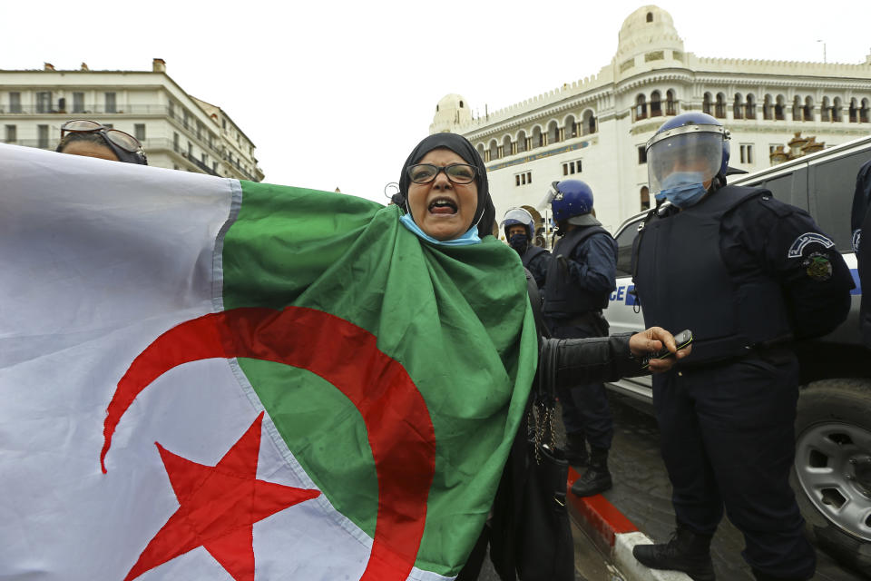 A woman holds an Algerian flag as Algerians demonstrate in Algiers to mark the second anniversary of the Hirak movement, Monday Feb. 22, 2021. February 22 marks the second anniversary of Hirak, the popular movement that led to the fall of Algerian President Abdelaziz Bouteflika. (AP Photo/Anis Belghoul)