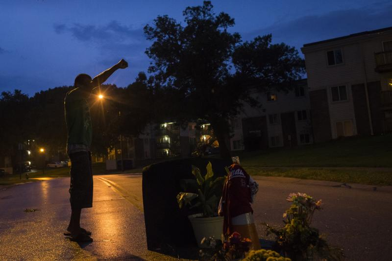 A local resident stands with his arm up over a makeshift memorial at the site where unarmed teen Michael Brown was shot dead in Ferguson, Missouri August 27, 2014. Authorities on Wednesday disbanded what had been a command center in Ferguson, Missouri, for law enforcement responding to sometimes violent protests over the killing of an unarmed black teenager by a white police officer. Officers loaded up the remaining fire trucks and police vans that were part of the temporary law enforcement headquarters in a strip mall parking lot, rolling out after several days of subdued demonstrations. REUTERS/Adrees Latif (UNITED STATES - Tags: CRIME LAW CIVIL UNREST)