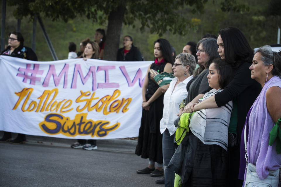 FILE - In this Aug. 29, 2017, file photo Nicole Matthews, second from right, of Minneapolis and her daughter Kiora Burgess-Matthews, attend a prayer circle for Savanna LaFontaine-Greywind at the Ramsey County Medical Examiner's office in St. Paul, Minn. People wore green ribbons to honor Savanna, her favorite color. Interior Secretary Deb Haaland as a former New Mexico congresswoman pushed for a law signed last year to address the crisis of missing, murdered and trafficked Indigenous women. The law, known as Savanna's Act, is intended to help law enforcement track, solve and prevent crimes against Native Americans, especially women and girls. The law is named for Savanna LaFontaine-Greywind, a member of the Spirit Lake tribe who was abducted and killed in 2017 near Fargo, North Dakota. (Leila Navidi/Star Tribune via AP, File)