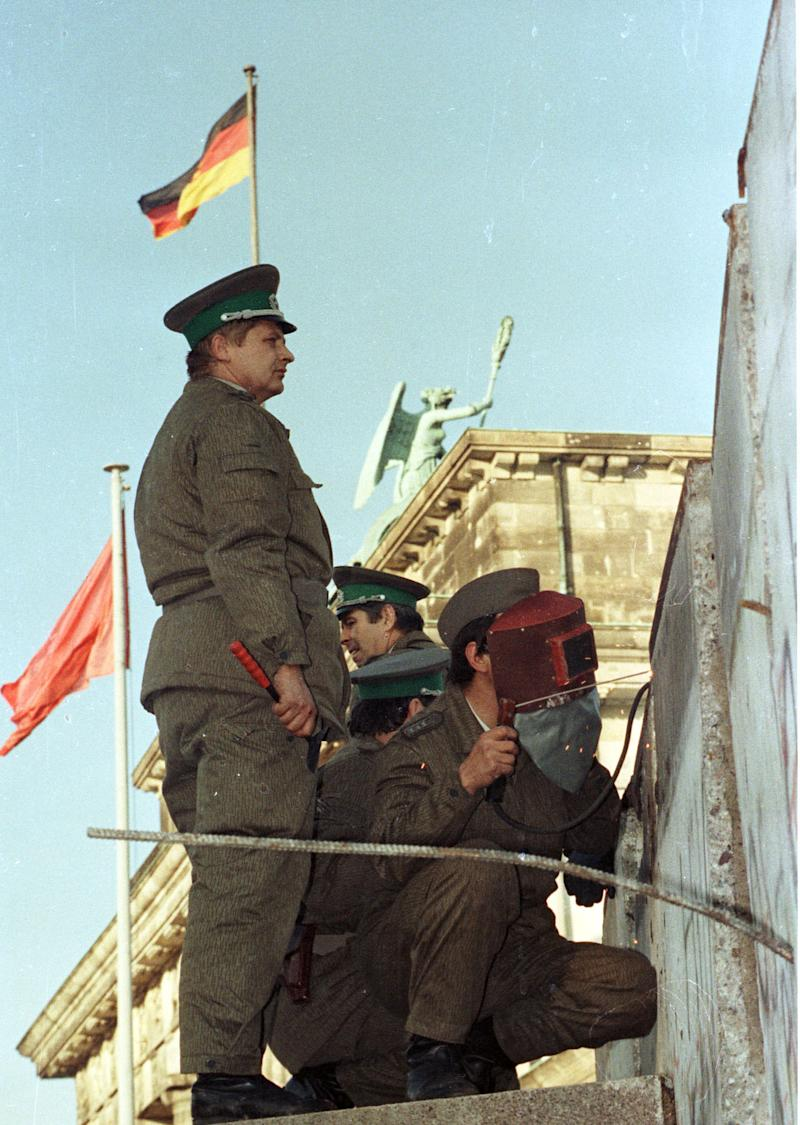 Border guards repair a section of the Berlin Wall, after protesters knocked it over earlier during the day, Nov. 11, 1989. (Photo: Wolfgang Rattay/Reuters)