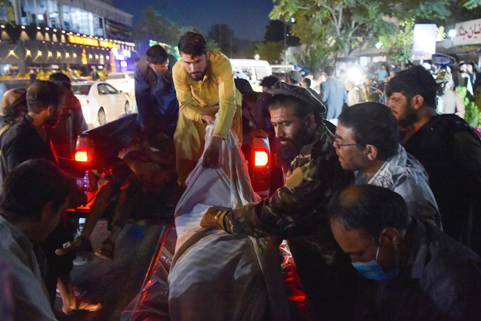 EDITORS NOTE: Graphic content / TOPSHOT - Volunteers and medical staff unload bodies from a pickup truck outside a hospital after two powerful explosions, which killed at least six people, outside the airport in Kabul on August 26, 2021. / AFP / Wakil KOHSAR