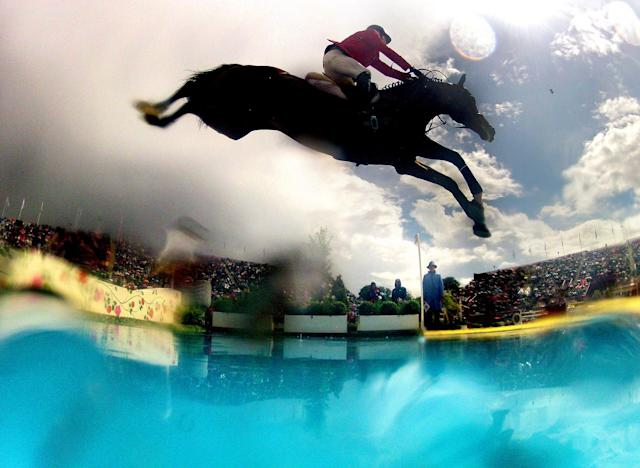 <p>In this photo made using a fisheye lens, Jaime Azcarraga, of Mexico, rides his horse Gangster, in the equestrian show jumping team competition at the 2012 Summer Olympics, Aug. 5, 2012, in London. (AP Photo/David Goldman) </p>