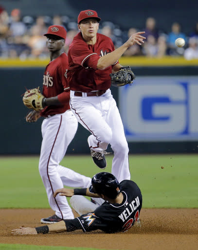 Miami Marlins' Christian Yelich is forced out by Arizona Diamondbacks' Nick Ahmed as he turns a double play on Marlins' Donovan Solano during the first inning of a baseball game, Wednesday, July 9, 2014, in Phoenix. (AP Photo/Matt York)