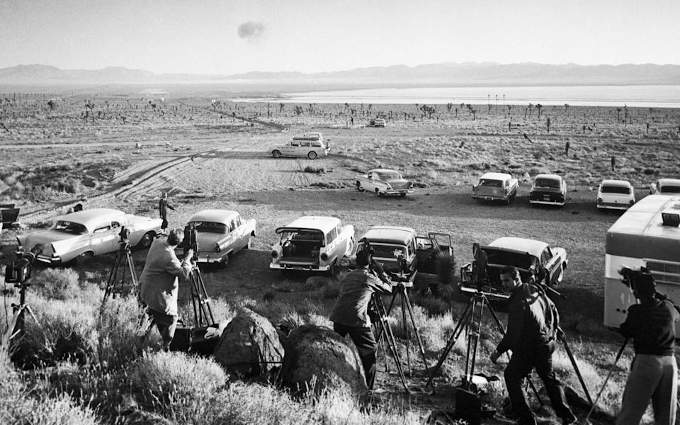 Reporters watch an explosion in 1958 - Getty