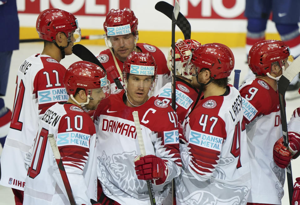 Denmark's team players celebrate victory after the Ice Hockey World Championship group A match between Britain and Denmark at the Olympic Sports Center in Riga, Latvia, Tuesday May 25, 2021. (AP Photo/Roman Koksarov)