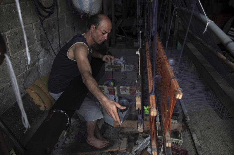 In this Saturday, July 6, 2019 photo, a Palestinian worker weaves carpets on a traditional wooden loom at a carpets factory in Gaza City. Talk about old Gaza, and what pops up are images of clay pottery, colorful glassware, bamboo furniture and ancient frame looms weaving bright rugs and mats. As such professions could be dying worldwide, the pace of their declining is too fast in Gaza that out of its some 500 looms, only one is still functioning. (AP Photo/Khalil Hamra)