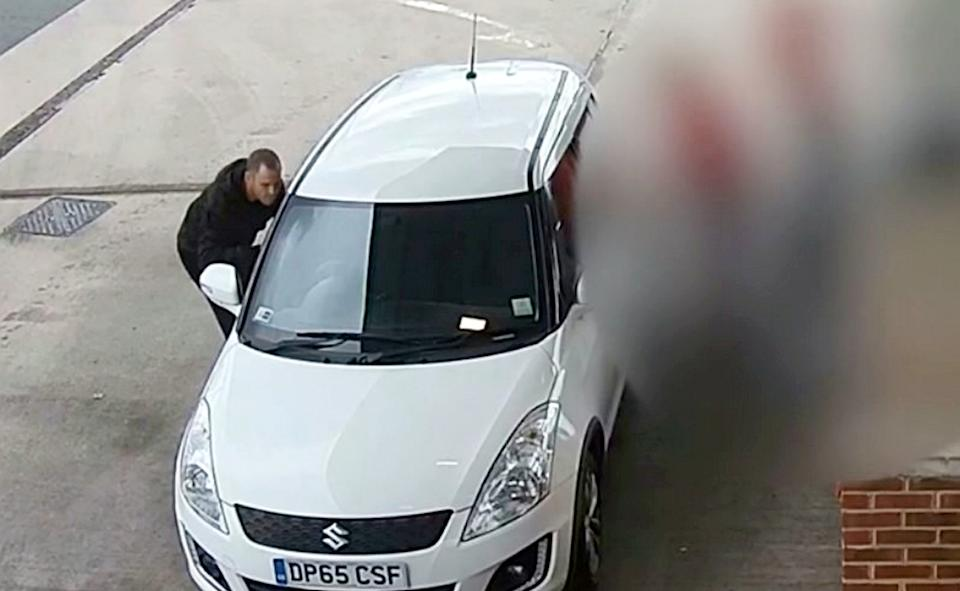 Car thief William Lewis peers into the window of a Suzuki Swift while the driver fills up the vehicle, in one of the many shocking thefts. (SWNS/West Midlands Police)