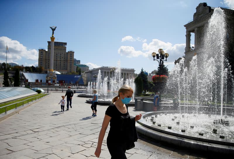 FILE PHOTO: Woman wearing a protective face mask walks in central Kiev
