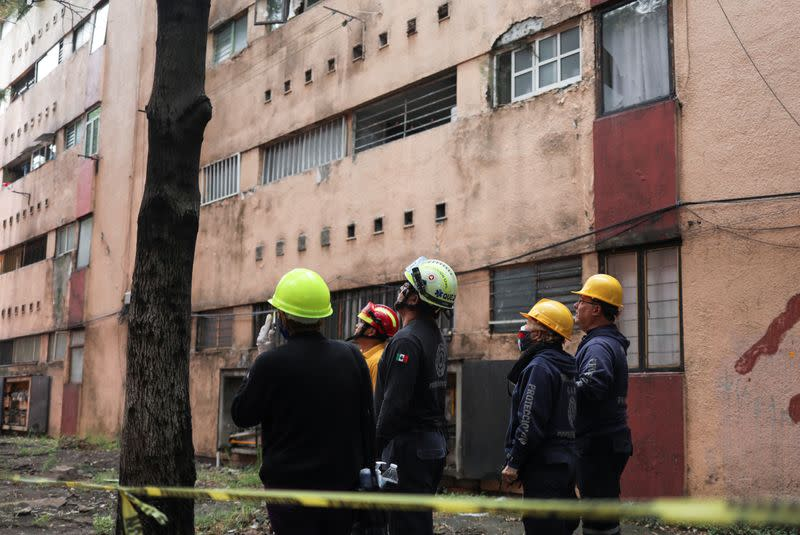 Members of Civil Protection check an apartment building damaged by an earthquake that struck southern Mexico on Tuesday, in Mexico City